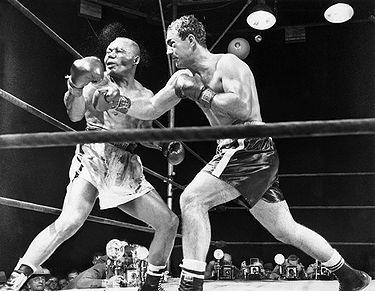 "23 Sep 1952, Philadelphia, Pennsylvania, USA --- Original caption: 9/24/52-Philadelphia, Pennsylvania: INP photographer Herb Scharfman was as precisely ""on the button"" as was the challenger when Rocky Marciano drove his right mercilessly to the jaw of champion Joe Walcott to knock him from his throne in the 13th round of last night's title fight at Philadelphia's Municipal Stadium. A cloudy spray of water and perspiration makes a partial halo around the head of the champion who was ""ex"" eleven seconds later. Note the ""mouse"" under Marciano's left eye. Ph: Herb Scharfman --- Image by © Bettmann/CORBIS"